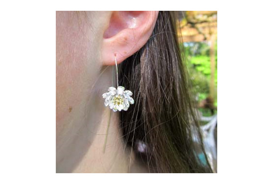 Sterling silver lotus flower drop earrings with a long stem behind the ears.
