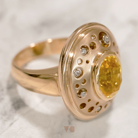 The yellow sapphire at the head of the ring orbited by small diamonds