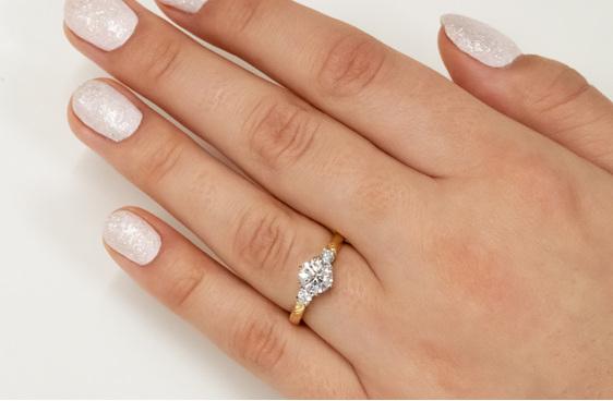Three stone diamond engagement ring with koru motif in band 18ct yellow gold