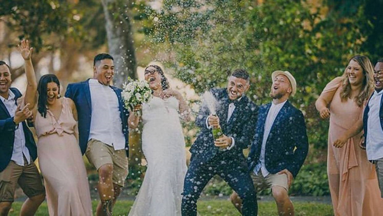 TJ and Greer popping a bottle of champagne with guests at their wedding