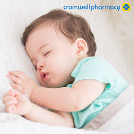 Toddler in blue tshirt sleeps soundly on his side eyes closed mouth open