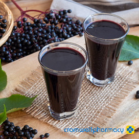 Two glasses of elderberry juice and a bunch of rich black berries are displayed.