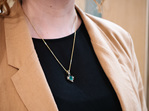 Two Tone Contemporary Design Emerald and Diamond Pendant showcased on model