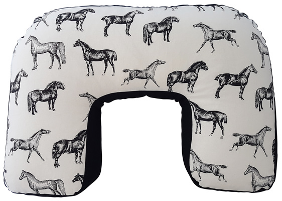 U shaped nursing pillow with a white  cover with black sketched horses on it