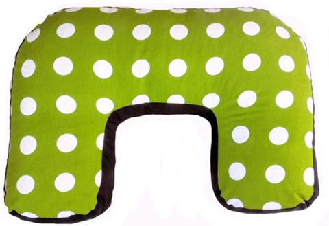 U shaped nursing pillow with green cover with white dots over it