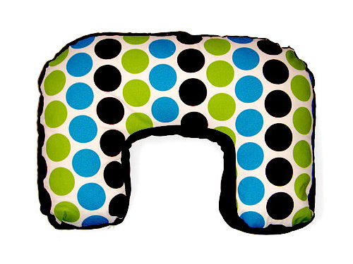 U shaped nursing pillow with lines of green, blue and black spots over it