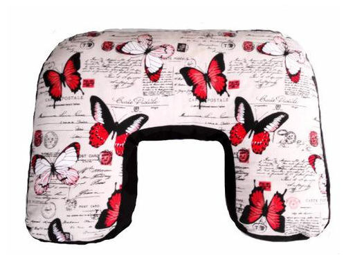 U shaped nursing pillow with postal stamps and red and white butterflys on it