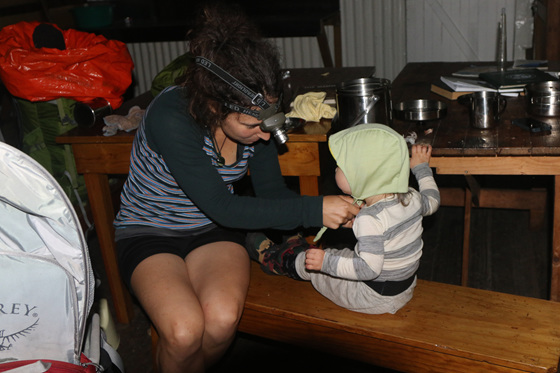 winter tramping doc hut interior with a toddler getting ready nz
