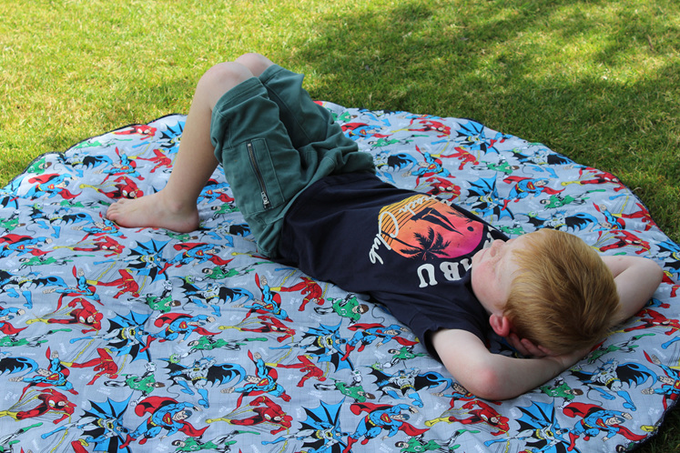 young boy relaxing on a babybaby super hero padded play mat