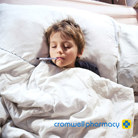 Young sick boy lying in bed with thermometer in mouth